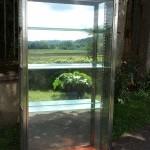 Ancienne vitrine verticale sur pieds.